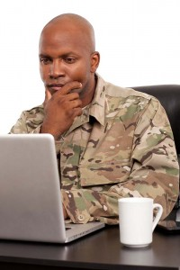 military servicemember looking at laptop computer