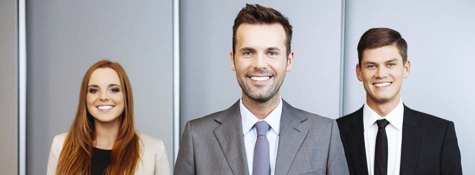 Three businesspeople in office attire smiling.