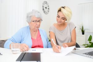Long-Term Care Adminstrator helping elderly woman with paperwork.