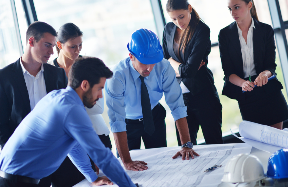 A team of professionals stand in a windowed office as a construction project manager discusses detailed printed plans laid across a table.