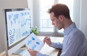 A business analyst reviews data to determine future strategies for his business.