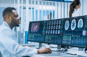 A medical scientist sits in from of an array of computer monitors studying research data.
