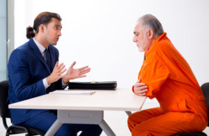 A young parole officer counsels a client on his upcoming parole. The officer started his forensic psychology career with an online degree from Touro University Worldwide.