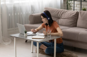 College student sits cross-legged at a coffee table with her laptop and notebook while listening to an online lecture.