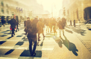 A busy city crosswalk crowded with anonymous people making their way home in the setting sun.