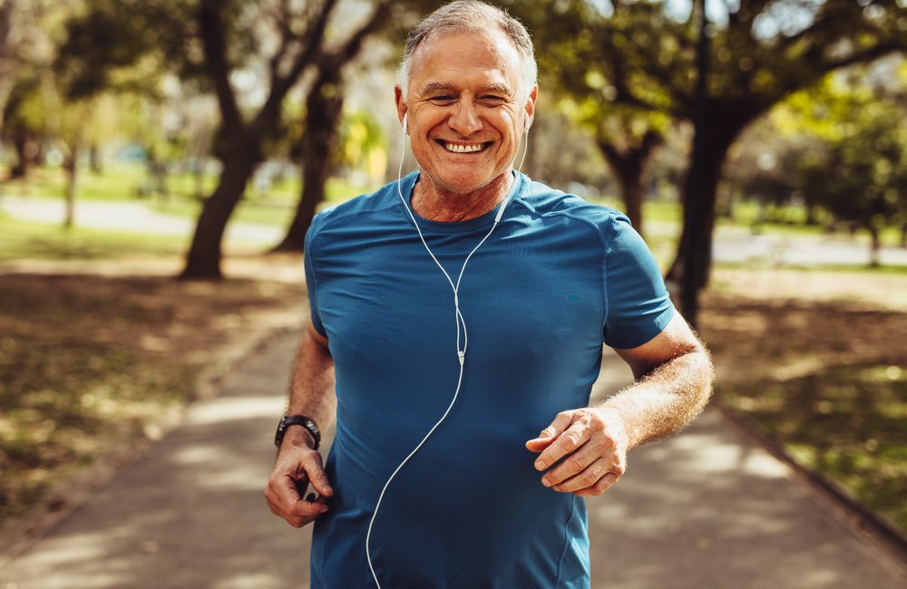 A smiling older man wearing earbuds jogs through a park while listening to a podcast.