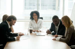 A skilled mediator sitting with two couples at a large conference table