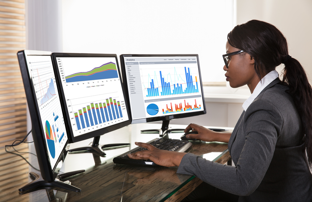 A business analyst reviews data to prepare a business strategy report.