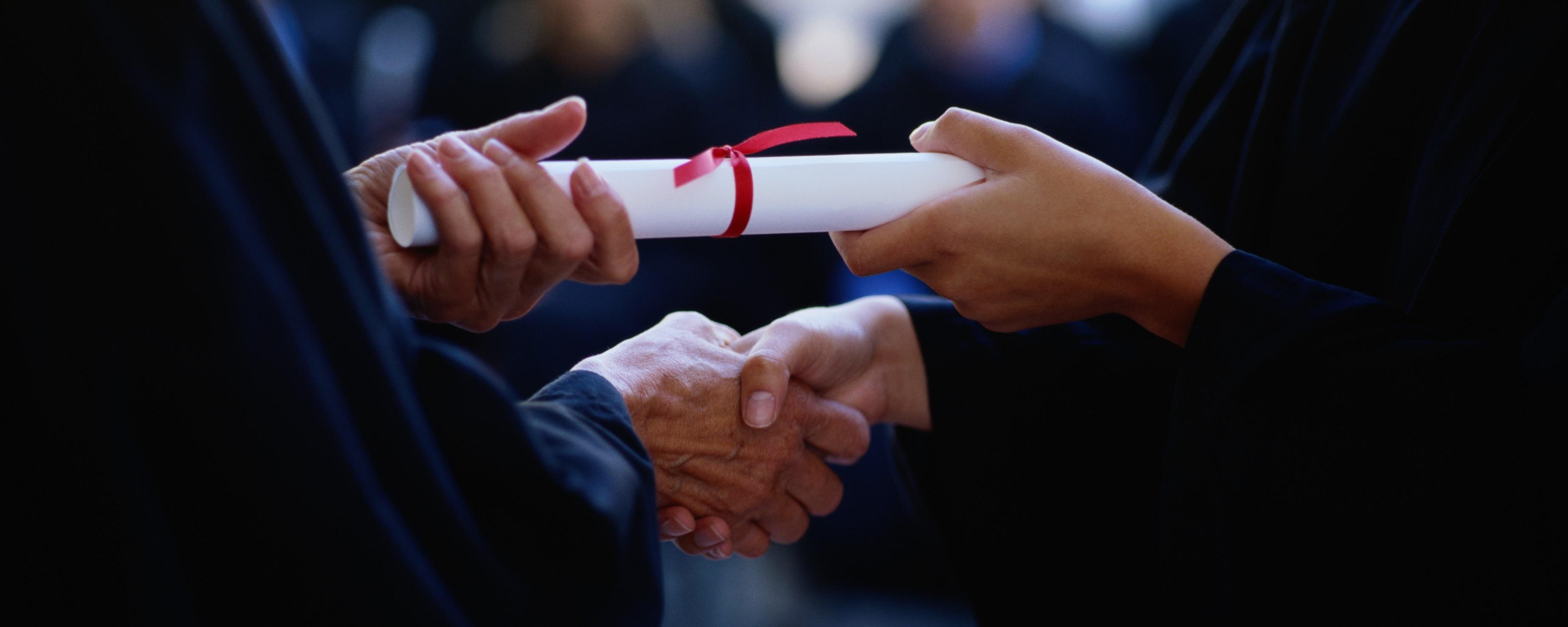 Graduate receiving a diploma, close-up of hands